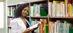 young african college student reading in library